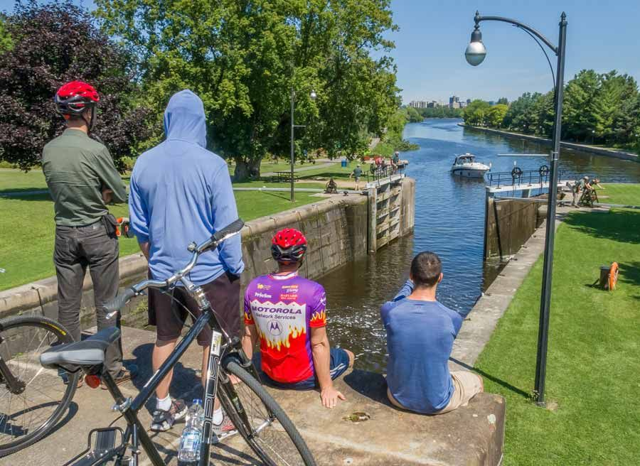 Participants sitting at a bench watching boats crossing Hartwells lock at Rideau Canal during best Ottawa bike tour by Escape