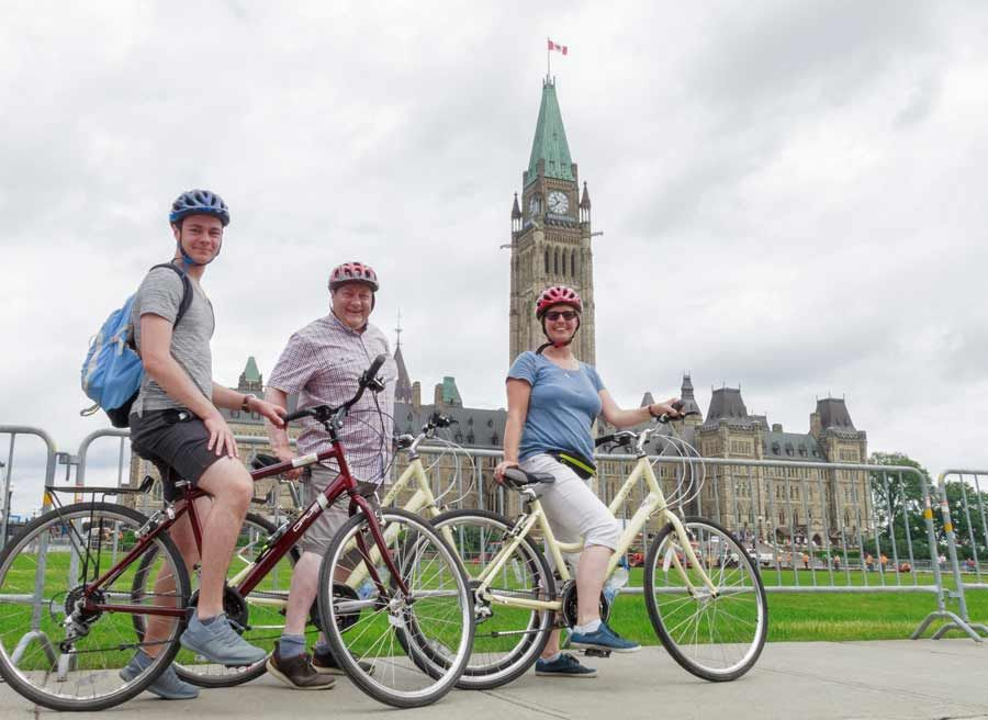 A family visits Parliament Hill and Peace Tower landmarks during best Ottawa bike tour in one day by Escape on Sparks