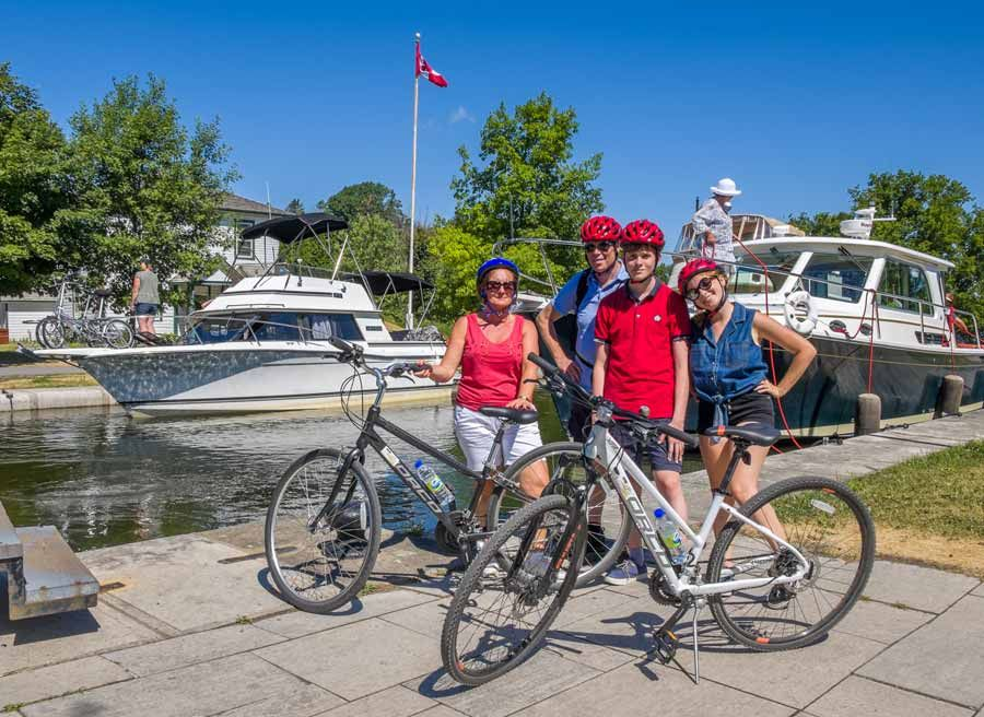 Family is taking a picture next to boats crossing Rideau Canal during bike & boat bike tours of Ottawa with escape on Sparks st.