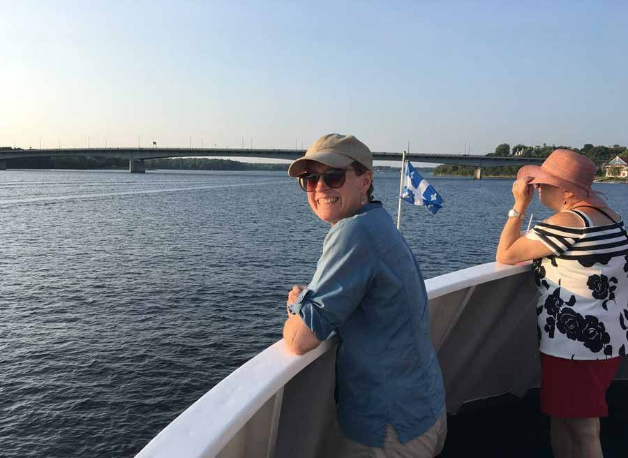 Boat cruise guest is looking at Ottawa River from the boat deck during bike & boat tour of Ottawa with Escape on Sparks