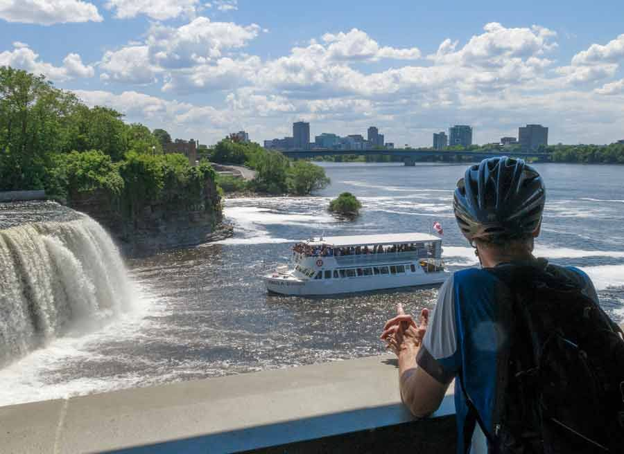 A participant is looking at boat cruise getting close to Rideau Falls Ottawa landmark during bike & boat tour with Escape