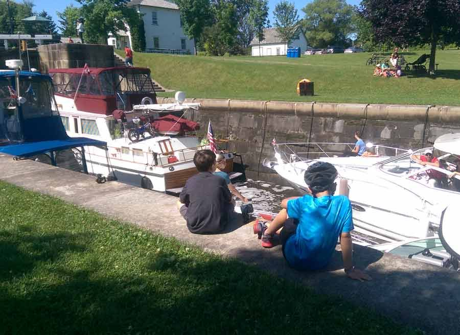 Kids sitting and watching boats crossing Rideau Canal locks during bike & boat bike tours of Ottawa with escape on Sparks