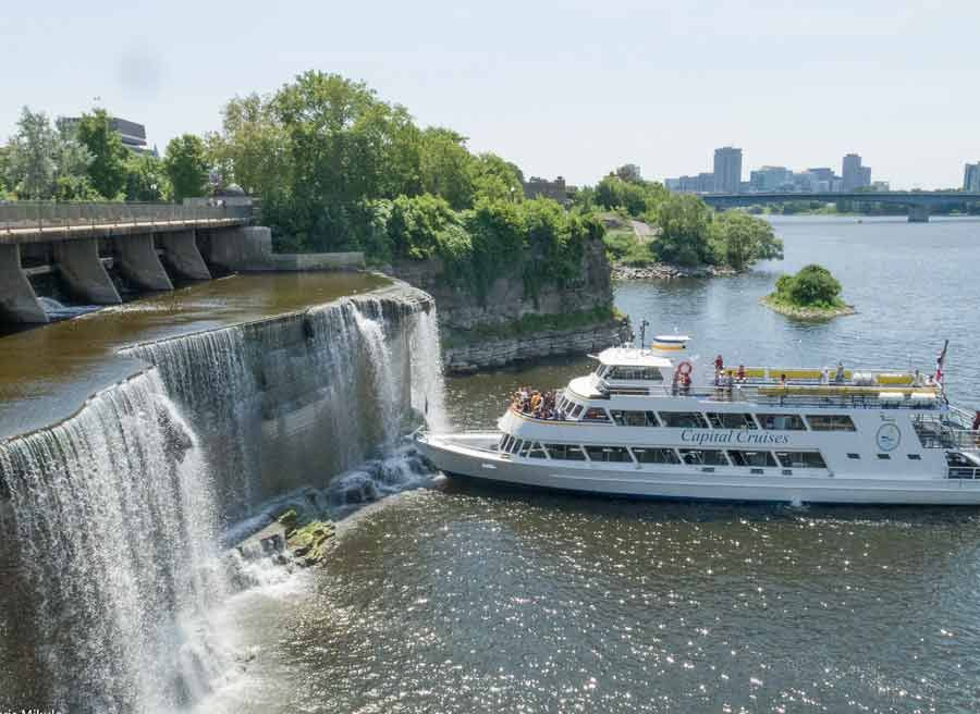 View of a boat cruise close to Rideau Falls Ottawa landmark on Ottawa River during bike & boat tour by Escape on Sparks