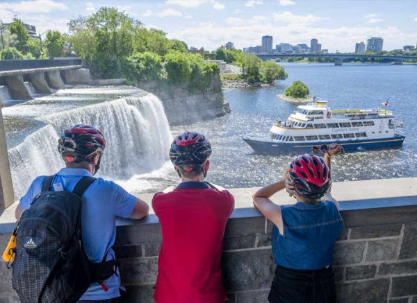 Guests are taking an Escape bike & boat tour and stop at Rideau Falls Ottawa landmark to watch a boat cruise
