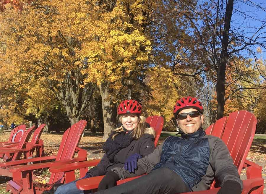 A couple is relaxing at adirondack chairs in a park during their bike and spa tour in ottawa with Escape tours and rentals