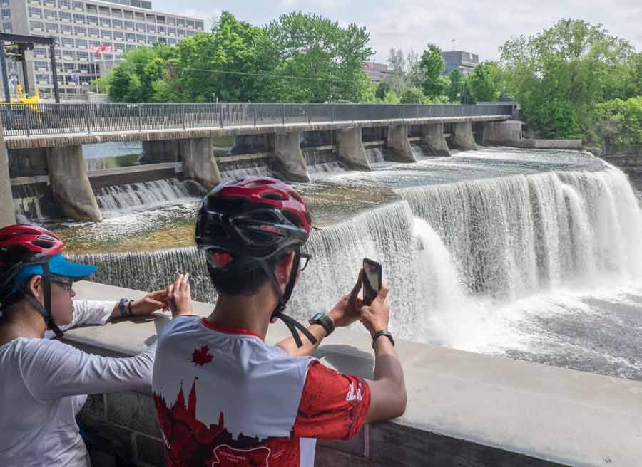 Guests are looking at Rideau falls during their bike and spa tour in Ottawa with Escape tours and rentals on Sparks