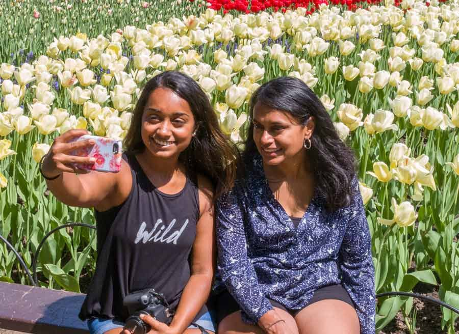 Friends are taking selfie in front of a tulip flower garden during Escape garden bike tour in Ottawa at Dow's Lake