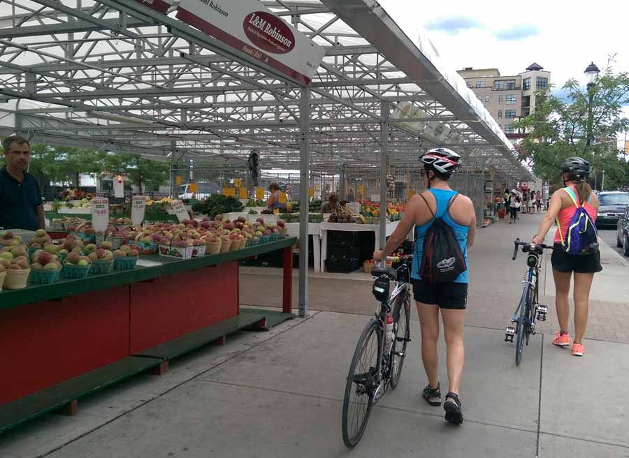 Guest are biking through Ottawa farmers' market during best of Ottawa Neighbourhood and nature bike tour with Escape