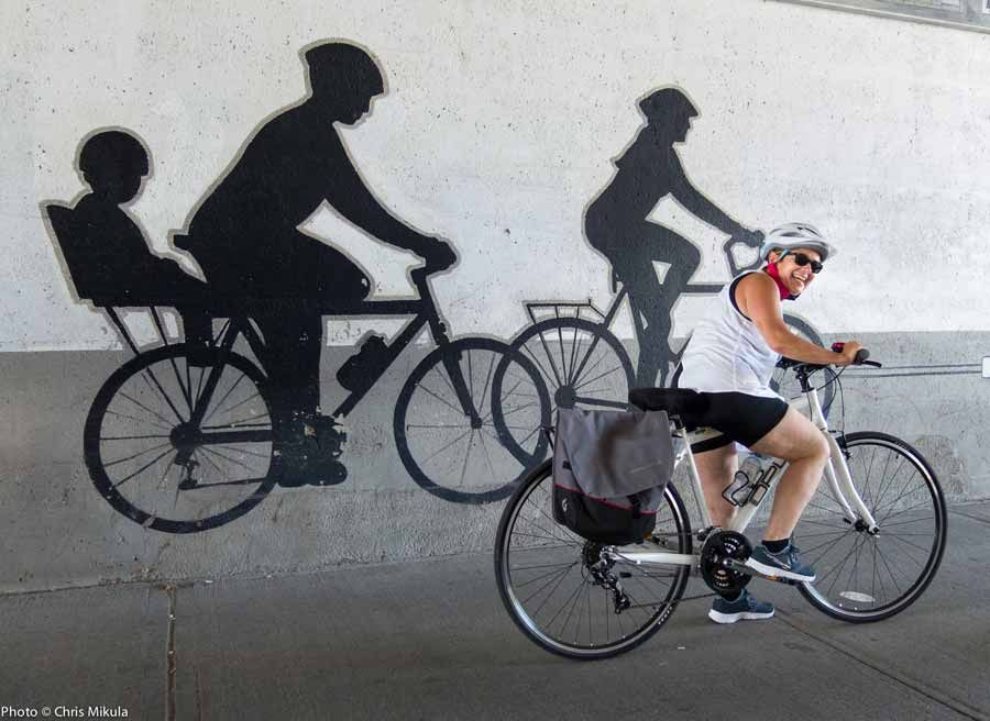 A guest is looking at biking street art mural in Little Italy during during best of Ottawa Neighbourhood and nature bike tour