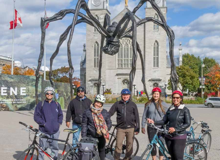 Guests taking picture in front of Spider Maman, Notre-Dame Cathedral Basilica during Escape Ottawa multi-day cycling tour