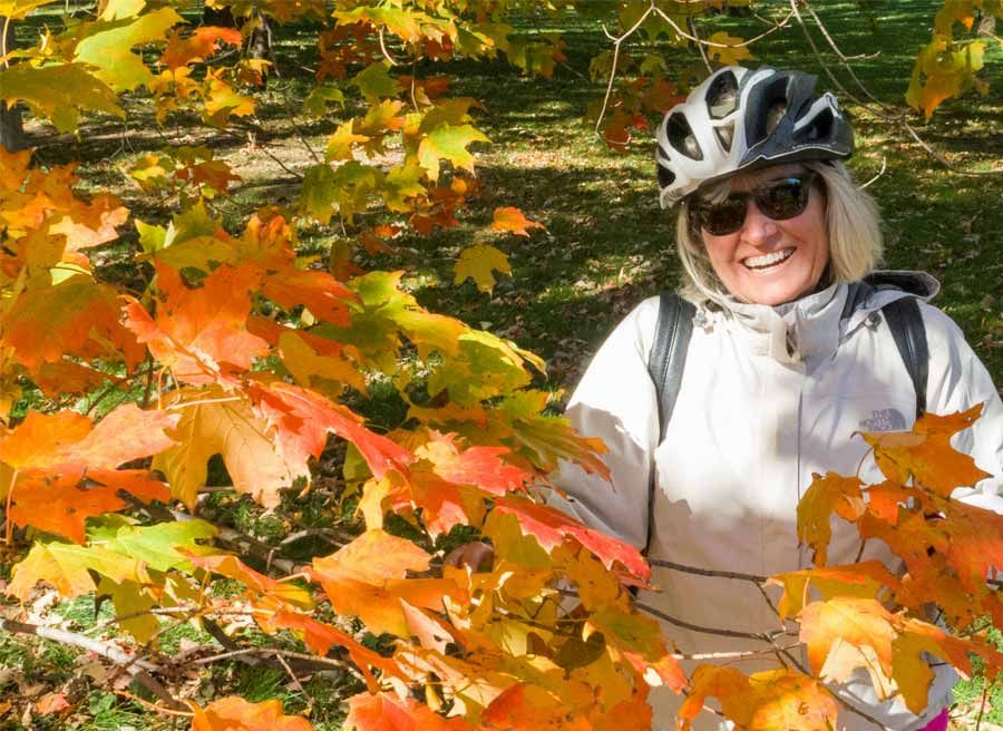 A guest smiling & taking a picture with Fall colours in Ottawa park during Ottawa multi-day cycling tour by Escape on Sparks