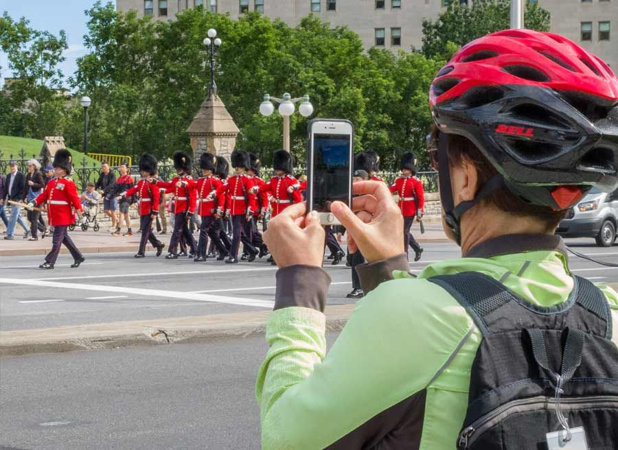 A guest is watching and taking a picture of the change of guard ceremony on Elgin st. during Ottawa highlights bike tour