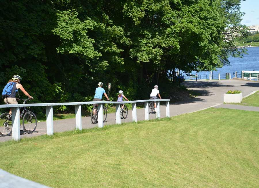 Small-group tour guests are cycling at Ottawa River Pathways on sunny day during Ottawa highlights bike tour by Escape