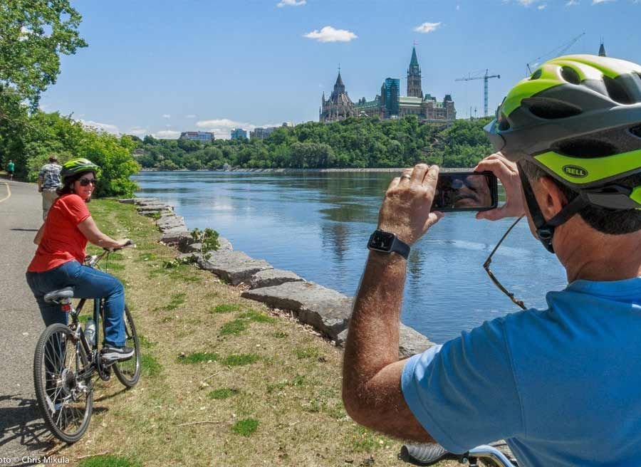 Guests have stopped at bike trail to take picture of Ottawa River and Parliament Building during Ottawa highlights bike tour