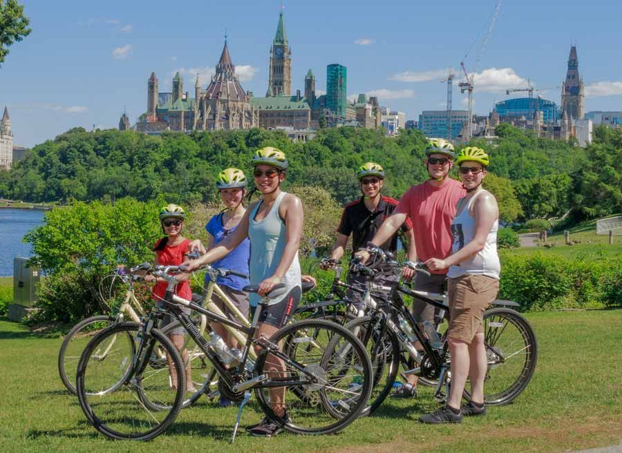 A corporate group taking a private Ottawa express bike tour and stop at Ottawa River path to see the view of the parliament