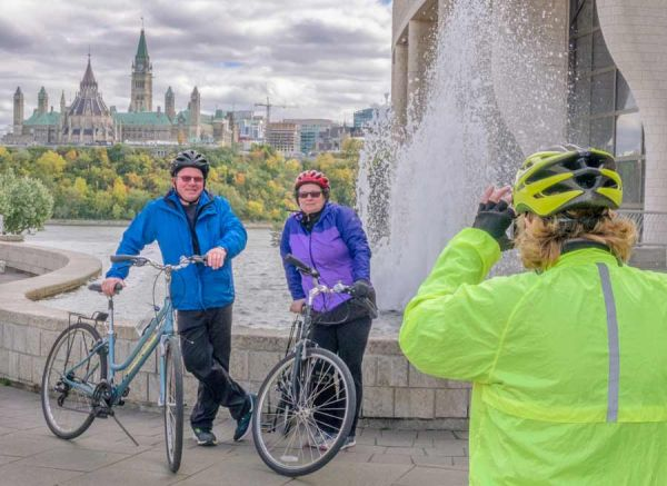Tour guide taking a picture of couple taking a bike tour in Ottawa