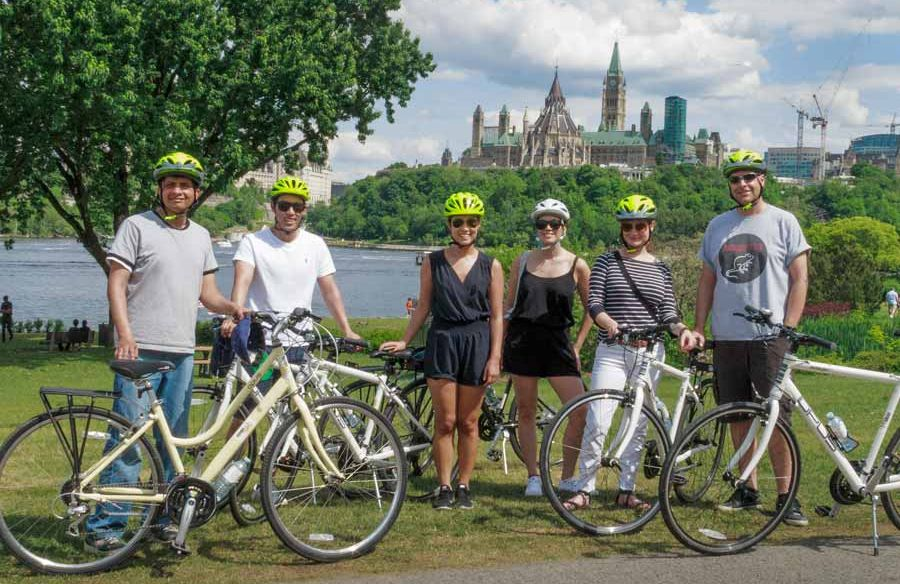Guests are taking a group picture with a view of Ottawa River and parliament building during a scheduled Ottawa bike tour with Escape