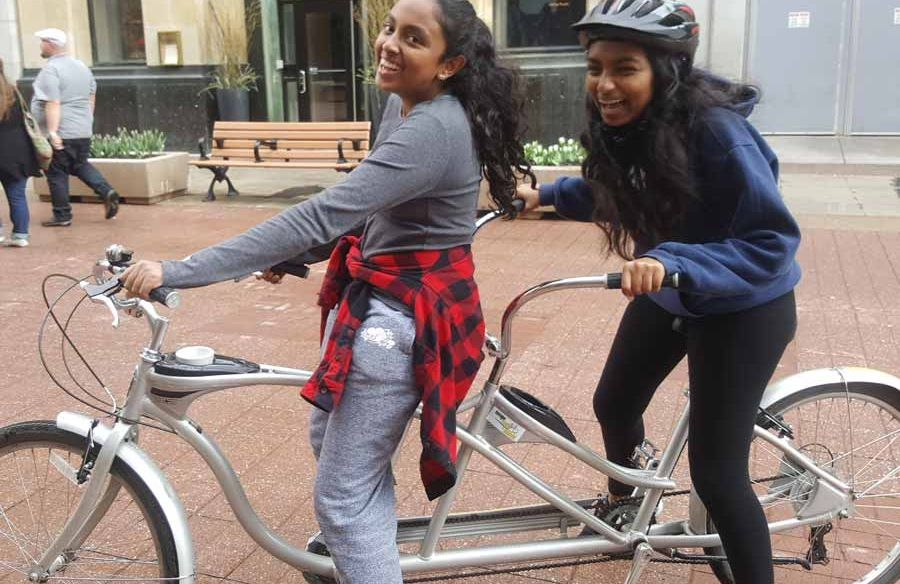 Friends laughing while riding a 2-person bike with Escape tandem bike rental on Sparks St., Ottawa