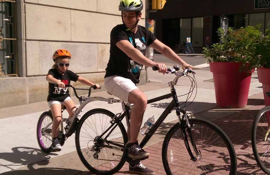 A parent is biking with the kid riding the rental trail-a-bike attached to his bike on Sparks St., Ottawa
