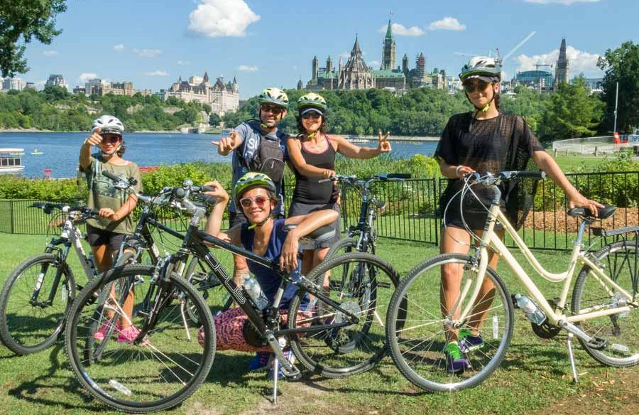 A family is enjoying an Ottawa tour by bike visiting landmarks with Escape Tours and Rentals